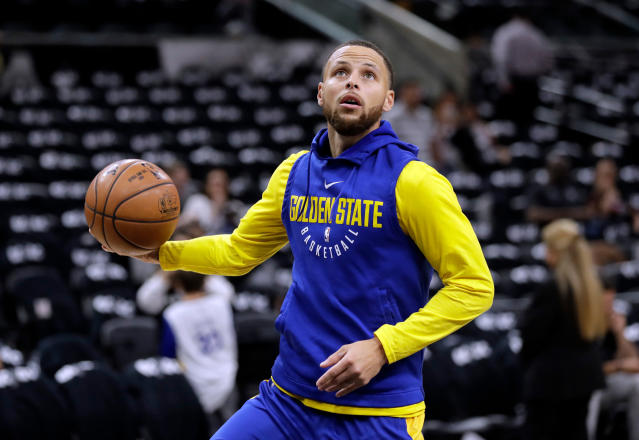 FILE - In this April 19, 2018 file photo, Golden State Warriors guard Stephen Curry (30) warms up before Game 3 of the team's first-round NBA basketball playoff series against the San Antonio Spurs in San Antonio. Curry has been cleared to take part in modified practices but will be out at least one more week with a left knee injury. The Warriors said Curry was examined by the team's medical staff Friday and is making progress in recovering from the grade 2 left MCL sprain that has sidelined him since March 23.(AP Photo/Eric Gay)