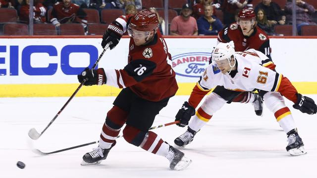 Arizona Coyotes left wing Max Domi (16) shoots a shot for a goal as he gets past Calgary Flames defenseman Brett Kulak (61) as Coyotes center Christian Dvorak (18) looks on during the second period of an NHL hockey game Monday, March 19, 2018, in Glendale, Ariz. (AP Photo/Ross D. Franklin)