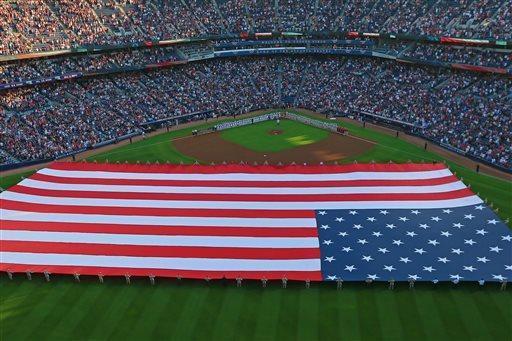 Soldiers cover the field with a United States flag as the Atlanta Braves and the Philadelphia Phillies line the field for their season opener baseball game on Monday, April 1, 2013, in Atlanta. (AP Photo/Atlanta Journal-Constitution, Curtis Compton)