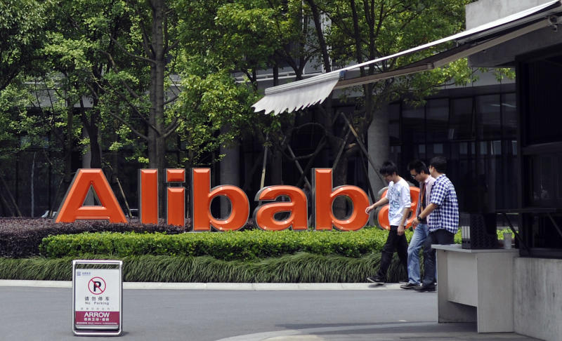 FILE - In this May 21, 2012 file photo, men walk past the corporate logo at the headquarters compound of Alibaba Group in Hangzhou in eastern China's Zhejiang province. Alibaba Group is aiming to raise $1 billion in a long-awaited IPO likely to have ripple effects across the Internet. The Tuesday, May 6, 2014 filing sets the stage for the technology industry's biggest initial public offering since short messaging service Twitter and its early investors collected $1.8 billion in its stock market debut last fall. (AP Photo/File) CHINA OUT