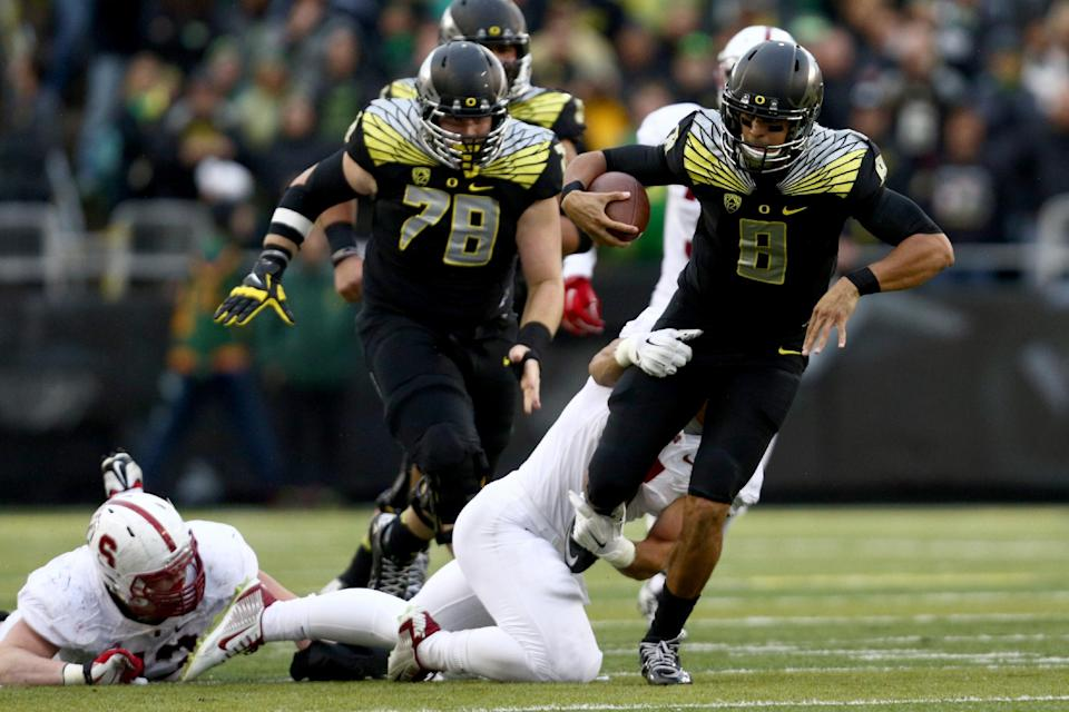 Oregon quarterback Marcus Mariota (8) tries to get away from the defender during the second quarter against Stanford in an NCAA college football game in Eugene, Ore., Saturday, Nov. 1, 2014. (AP Photo/Ryan Kang)