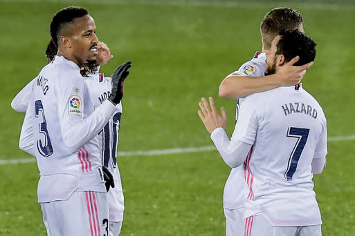 Real Madrid's Eden Hazard, right, celebrates after scoring his side's third goal during the Spanish La Liga soccer match between Alaves and Real Madrid at Mendizorroza stadium in Vitoria, Spain, Saturday, Jan. 23, 2021. (AP Photo/Alvaro Barrientos)