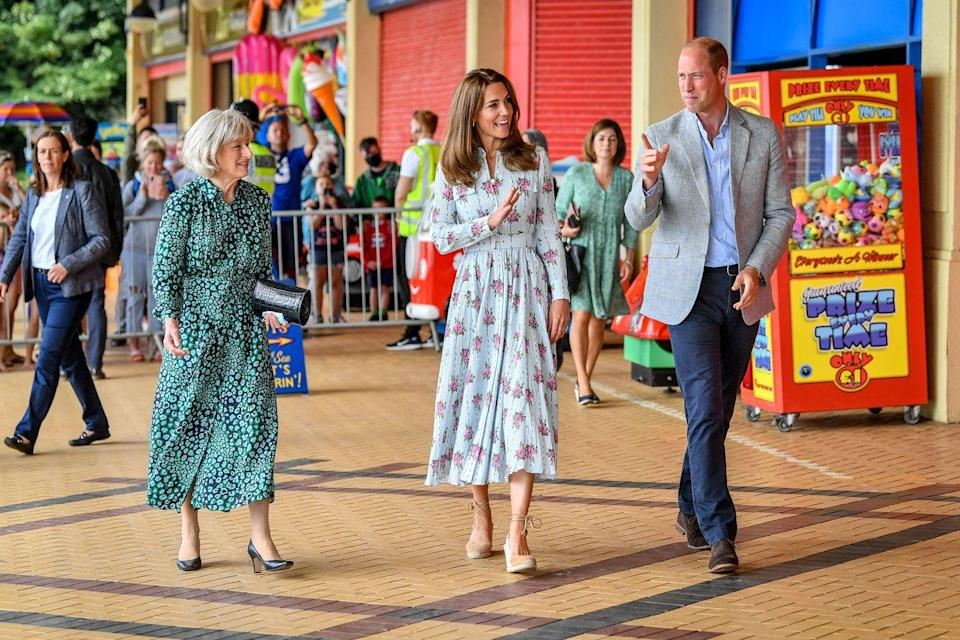 "<p>For a visit to South Wales, Kate chose an Emilia Wickstead belted, floral midi dress. She paired the look with brown suede espadrilles and, when she was indoors, her liberty print face mask. Luckily, the dress proved flexible enough for Kate to engage in some <a href=""https://www.townandcountrymag.com/society/tradition/a33521295/kate-middleton-prince-william-arcade-games-barry-island-video-photos/"" rel=""nofollow noopener"" target=""_blank"" data-ylk=""slk:intense arcade games"" class=""link rapid-noclick-resp"">intense arcade games</a>. </p>"