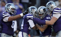 Kansas State running back Charles Jones (24) is congratulated by teammates offensive lineman Matt Kleinsorge (65), fullback Glenn Gronkowski (48) and offensive lineman Drew Liddle (61) after a touchdown during the first half of an NCAA college football game against Kansas in Manhattan, Kan., Saturday, Nov. 29, 2014. (AP Photo/Orlin Wagner)