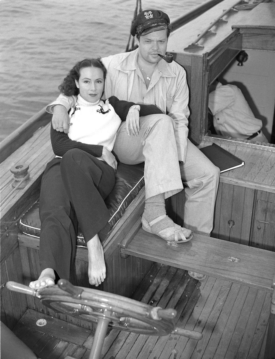 <p>Dolores del Río and Orson Welles enjoy a day on the water, making use of the stern of their ship for a photo op. The actress casually places her foot on the wheel of the ship, as Welles smokes a pipe. </p>