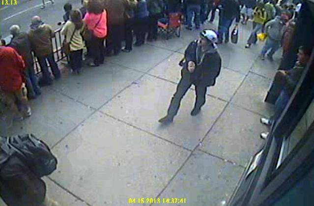 This frame grab from a video released by the FBI on Thursday, April 18, 2013, shows what the FBI are calling suspect number 1, front barely visible at bottom left, and suspect number 2, in white cap, back right, walking near each other through the crowd in Boston on Monday, April 15, 2013, before the explosions at the Boston Marathon. (AP Photo/FBI)