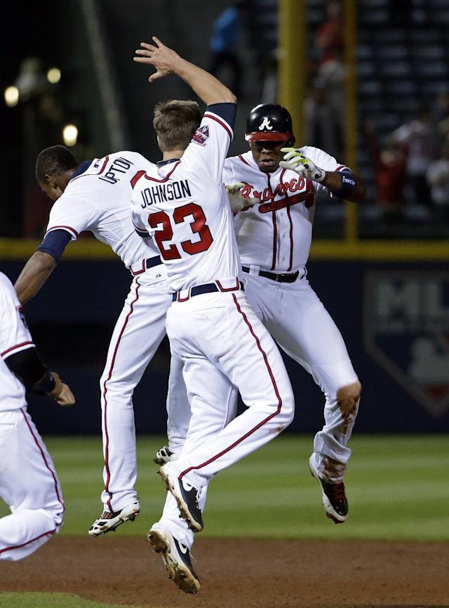 Atlanta Braves' Justin Upton, right, celebrates with teammates B.J. Upton, left, and Chris Johnson after hitting a single to score the winning run in the tenth inning of a baseball game against the Washington Nationals, Friday, April 11, 2014, in Atlanta. (AP Photo/David Goldman)