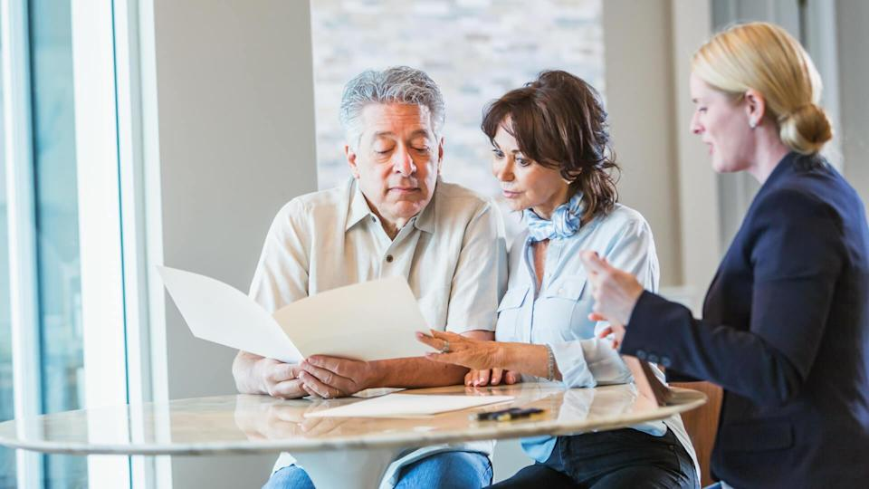 A senior couple sitting down with a personal consultant, perhaps a financial advisor to discuss their retirement plans, or maybe a realtor or insurance agent.
