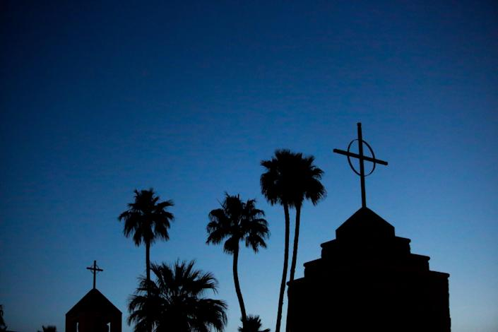 The sun begins to rise behind a California church. Singing or chanting isn't permitted in houses of worship in the Golden State to help the coronavirus from spreading, but that isn't stopping everyone.