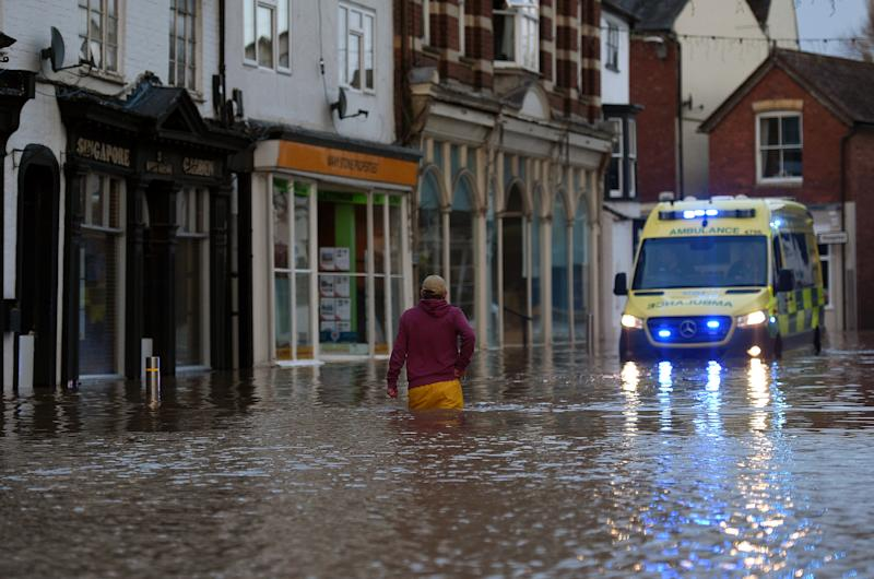 A man wades through flood water towards an ambulance in a flooded street in Tenbury Wells, after the River Teme burst its banks in western England, on February 16, 2020, after Storm Dennis caused flooding across large swathes of Britain. - A man died after falling into a river on Sunday as Storm Dennis swept across Britain with the army drafted in to help deal with heavy flooding and high winds. (Photo by Oli SCARFF / AFP) (Photo by OLI SCARFF/AFP via Getty Images)