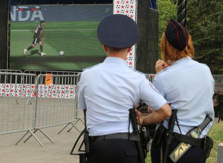 Soccer Football - World Cup - Group D - Argentina vs Iceland - Simferopol, Crimea - June 16, 2018. Police officers watch the match in a city park. REUTERS/Pavel Rebrov