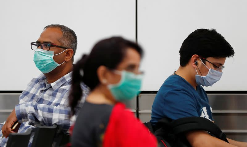 Passengers wearing protective masks sit at an airport terminal following an outbreak of the coronavirus disease (COVID-19), in New Delhi