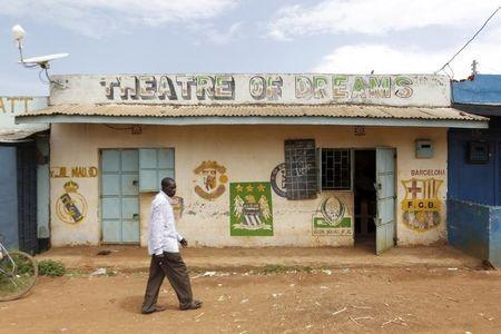 "A man walks past the local ""Theatre of Dreams"" cinema hall within the trading centre near the ancestral home of U.S. President Barack Obama in Nyang'oma village in Kogelo west of Kenya's capital Nairobi"