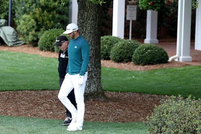 Dustin Johnson of the United States walks with coach Butch Harmon to the practice range during the first round of the 2017 Masters Tournament at Augusta National Golf Club on April 6, 2017 in Augusta, Georgia (AFP Photo/Rob Carr)