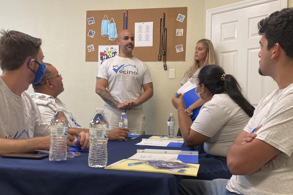 Alex Berrios, left, and Devon Murphy-Anderson, right, co-founders of the nonprofit Mi Vecino, coach newly hired staff members on how best to approach people and convince them to register to vote on June 24, 2021, in Kissimmee, Fla. Their group, and other advocacy organizations affiliated with Democrats, are trying to engage Latino voters earlier and build lasting relationships after Republicans gained ground with voters in some Latino communities during last year's presidential and congressional races. (AP Photo/Will Weissert)