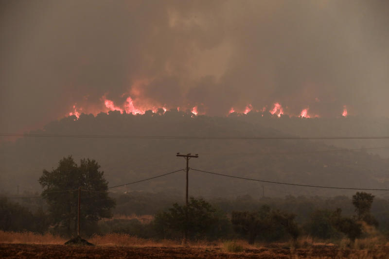 Flames rise from a forest fire at Psachna village on the island of Evia, northeast of Athens, Tuesday, Aug. 13, 2019. Dozens of firefighters backed by water-dropping aircraft are battling a wildfire on an island north of Athens that has left the Greek capital blanketed in smoke. (AP Photo/Yorgos Karahalis)