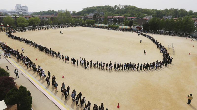 People form a long line to pay their silent tribute to the victims of the sunken ferry Sewol at the Olympic Memorial Museum in Ansan, South Korea, Saturday, April 26, 2014. All 15 people involved in navigating the boat that sank and left scores of people dead or missing are now in custody after authorities on Saturday detained four more crew members, a prosecutor said. (AP Photo/Yonhap) KOREA OUT
