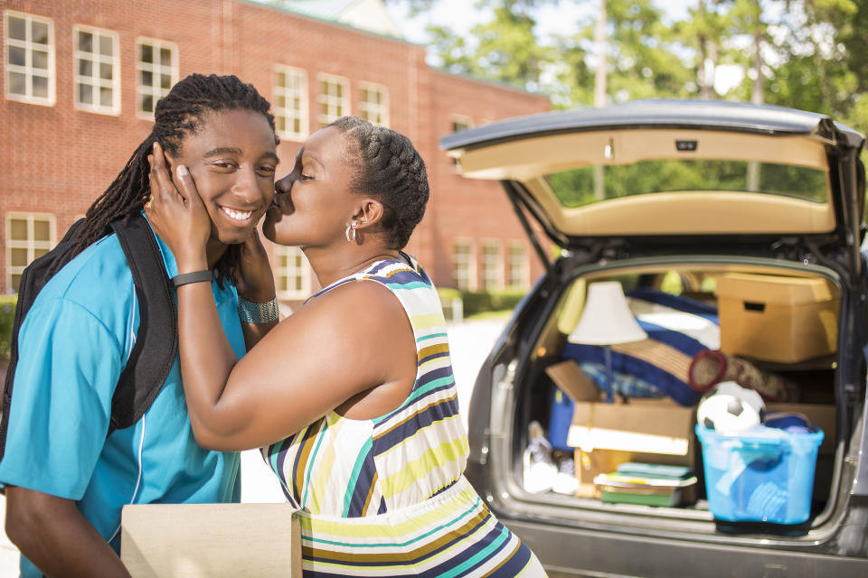African descent boy heads off to college.  The 18-year-olds' mother is helping him unpack his car and says goodbye with a kiss as he moves into the college campus dorm.  He is excited to start his school adventures. He  carries backpack and textbooks.  Family events.  Back to school.