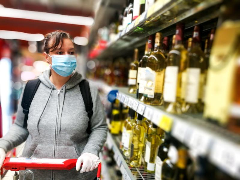 Selective focus color image depicting a caucasian woman in her 30s wearing a protective surgical face mask and plastic surgical gloves during the coronavirus (Covid-19) pandemic, in a bid to stop the spread of the virus. The woman is pushing her shopping cart inside a supermarket while shopping for wine and alcohol in the alcoholic drinks section of the store. Room for copy space. (Photo: coldsnowstorm via Getty Images)