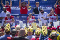Winner Michelle Lesco, center, competes in the Nathan's Famous Fourth of July International Hot Dog-Eating Contest in Coney Island's Maimonides Park on Sunday, July 4, 2021, in Brooklyn, New York. (AP Photo/Brittainy Newman)
