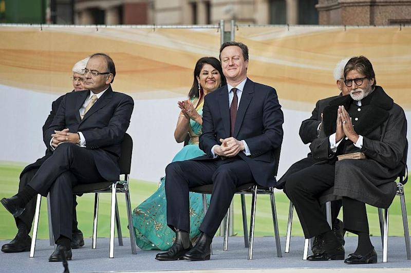 David Cameron (centre) and Bollywood actor Amitabh Bachchan (right) sit side-by-side at a 2015 ceremony unveiling a statue of Mahatma Gandhi (AFP via Getty Images)
