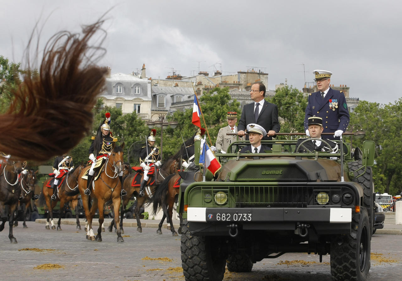 French President Francois Hollande, center, alongside French Chief Staff Admiral Edouard Guillaud review the troops during the Bastille Day military parade on the Champs Elysees avenue, Paris, Saturday, July 14, 2012. (AP Photo/Jacques Brinon, Pool)