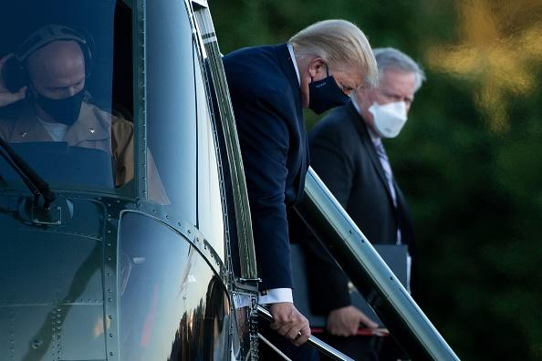 White House Chief of Staff Mark Meadows (R) watches as US President Donald Trump walks off Marine One while arriving at Walter Reed Medical Center in Bethesda, Maryland.