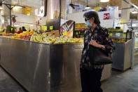 A woman walks past a produce stand at the Grand Central Market, Monday, Nov. 16, 2020, in Los Angeles. Gov. Gavin Newsom announced Monday, Nov. 16, 2020, that due to the rise of COVID-19 cases, some counties have been moved to the state's most restrictive set of rules. The new rules begin Tuesday, Nov. 17. (AP Photo/Marcio Jose Sanchez)