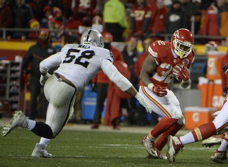 Jan 3, 2016; Kansas City, MO, USA; Kansas City Chiefs running back Spencer Ware (32) carries the ball against Oakland Raiders defensive end Khalil Mack (52) in the second half at Arrowhead Stadium. Kansas City won the game 23-17. Mandatory Credit: John Rieger-USA TODAY Sports / Reuters Picture Supplied by Action Images