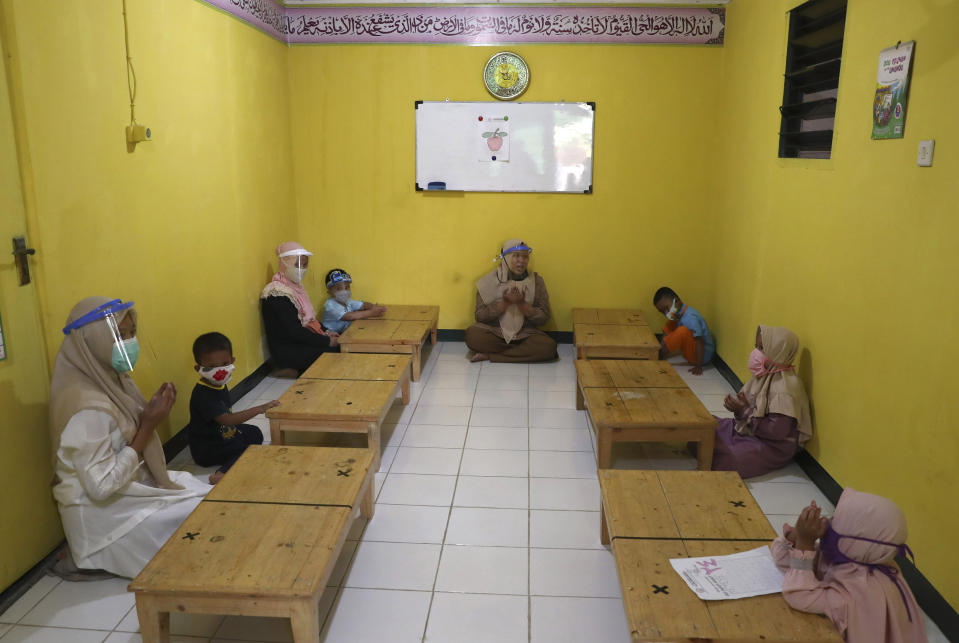 Teachers and students wearing protective gear as a precaution against the new coronavirus outbreak pray during a class at a Quran educational facility outside Jakarta, Indonesia, Wednesday, July 1, 2020. The government of Indonesia's capital region is extending the first transition phase from large-scale social restrictions in Jakarta as the number of new confirmed coronavirus cases continues to rise. (AP Photo/Tatan Syuflana)
