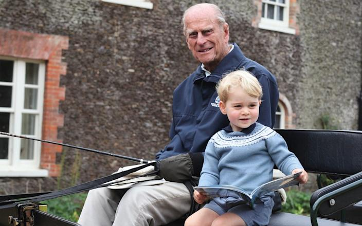The infant Prince George enjoys a carriage drive alongside his great-grandfather