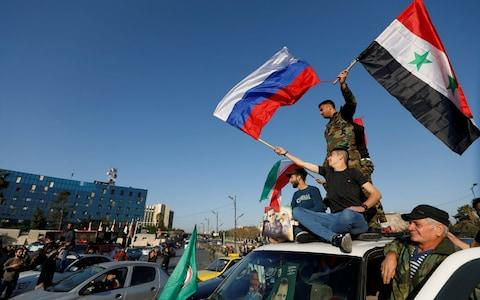 Syrians wave Russian and Syrian flags during a protest against U.S.-led air strikes in Damascus - Credit: Reuters