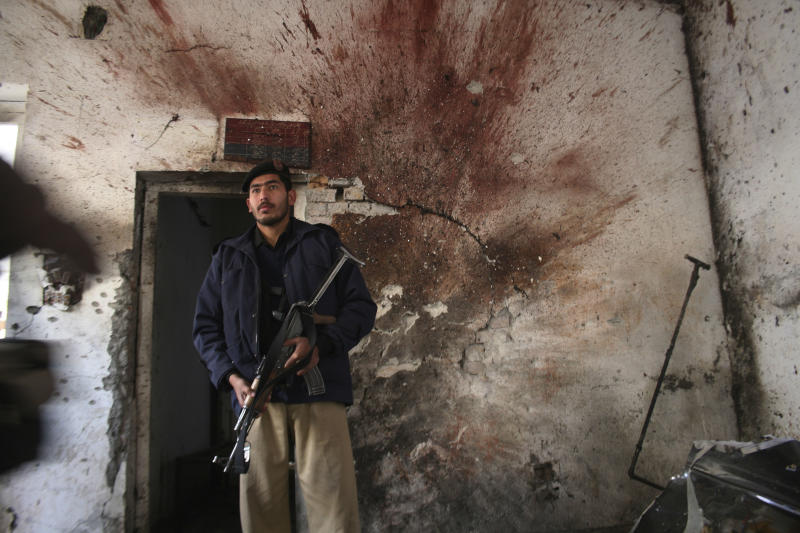 A Pakistani police officers stands at a police station after suicide attacks in Peshawar, Pakistan on Friday, Feb. 24, 2012. Suicide bombers armed with assault rifles and grenades attacked a large police station in the northwestern Pakistan city of Peshawar early Friday, killing three officers in an assault authorities said was likely in revenge for offensives against nearby strongholds.(AP Photo/Mohammad Sajjad)