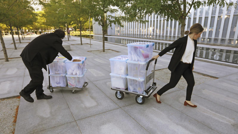 Officials wheel evidence in to the federal courthouse Monday, Aug. 12, 2019, in Salt Lake City. Former Eagle Scout Aaron Shamo, 29, will stand trial on allegations that he and a small group of fellow millennials ran a multimillion-dollar empire from the basement of his suburban Salt Lake City home by trafficking hundreds of thousands of pills containing fentanyl, the potent synthetic opioid that has exacerbated the country's overdose epidemic in recent years. (AP Photo/Rick Bowmer)