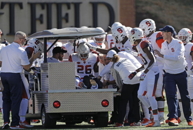 """Teammates console Syracuse's <a class=""""link rapid-noclick-resp"""" href=""""/ncaaf/players/256895/"""" data-ylk=""""slk:Tyrone Perkins"""">Tyrone Perkins</a> (26) after he was injured in the first half of an NCAA college football game against Wake Forest in Charlotte, N.C., Saturday, Nov. 3, 2018. (AP Photo/Chuck Burton)"""