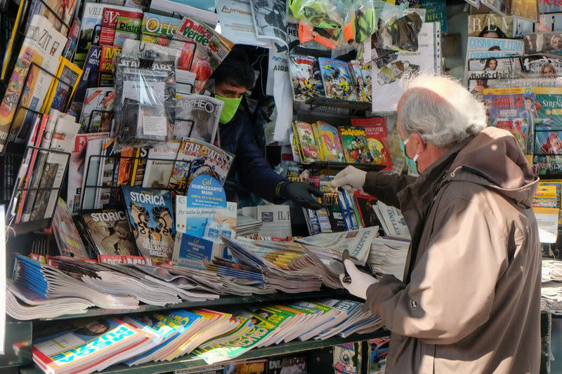 FILE PHOTO: A man wears a protective face mask and gloves at the newsstand as the Italian government allows the reopening of some shops while a nationwide lockdown continues following the outbreak of the coronavirus disease (COVID-19) in Venice