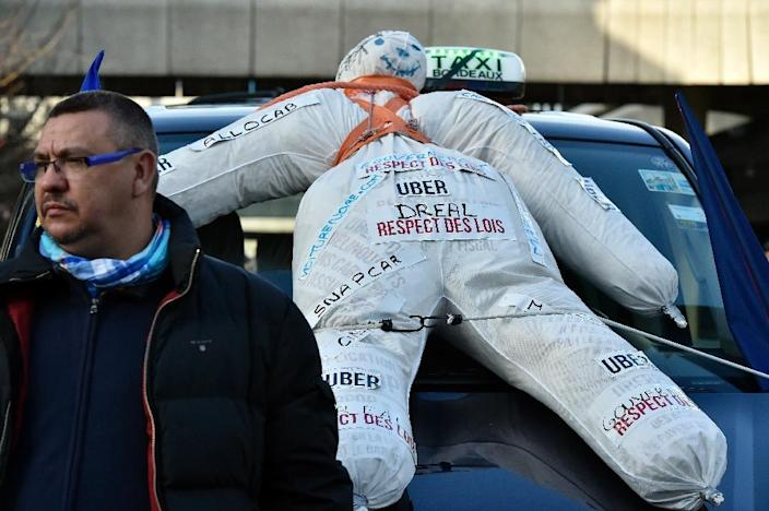 A dummy is fixed to the hood of a taxi car as taxi drivers block a street near the Prefecture in Bordeaux, southwestern France, on January 26, 2016 (AFP Photo/Georges Gobet)