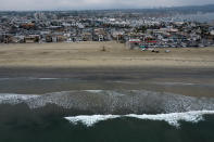 FILE - This Thursday, Oct. 7, 2021, aerial file photo taken with a drone, shows the closed beach after an oil washed up on a beach in Newport Beach, Calif. The amount of crude oil spilled in an offshore pipeline leak in Southern California is believed to be close to about 25,000 gallons, a Coast Guard official said Thursday Oct. 14, 2021. (AP Photo/Ringo H.W. Chiu, File)