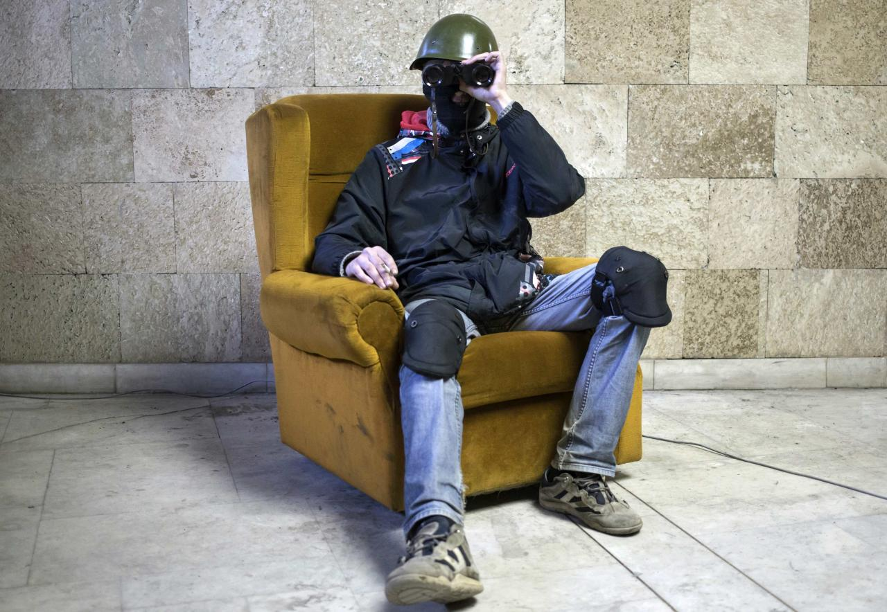 A masked pro-Russian protester poses with a pair of binoculars inside a regional government building in Donetsk, eastern Ukraine April 25, 2014. Picture taken April 25, 2014. REUTERS/Marko Djurica (UKRAINE - Tags: POLITICS CIVIL UNREST PORTRAIT)