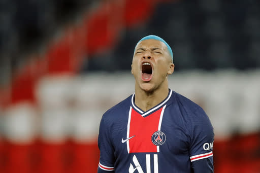 PSG's Kylian Mbappe reacts after missing a goal during the French League One soccer match between Paris Saint-Germain and Lorient at the Parc des Princes in Paris, France, Wednesday, Dec. 16, 2020. (AP Photo/Christophe Ena)