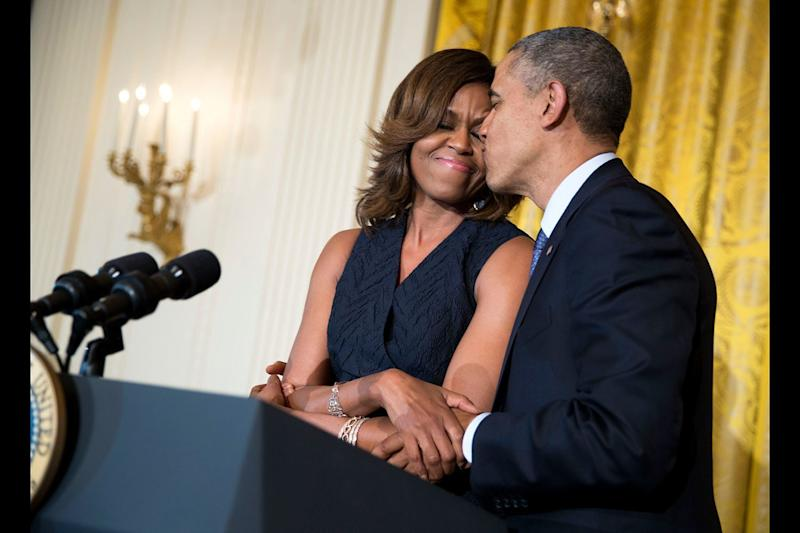 President Barack Obama kisses first lady Michelle Obama during her remarks at an Affordable Care Act reception in the East Room of the White House on May 1, 2014.