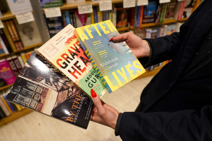 A member of staff holds copies of books by Zanzibar-born novelist Abdulrazak Gurnah in a book shop in London, Thursday, Oct. 7, 2021. U.K.-based Tanzanian writer Abdulrazak Gurnah, whose experience of crossing continents and cultures has fed his novels about the impact of migration on individuals and societies, won the Nobel Prize for Literature on Thursday. (AP Photo/Alberto Pezzali)