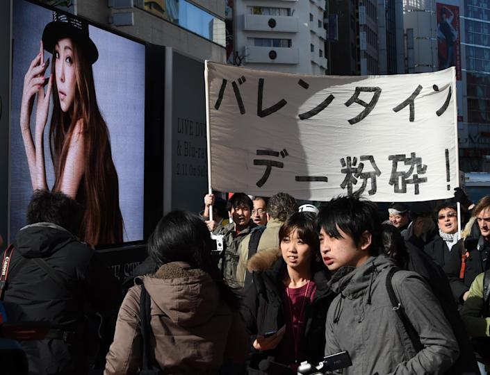 Ten killjoys, holding a banner saying 'Smash Valentine's Day', march next to an advertisement of Japanese singer Namie Amuro (L), during a demonstration in Tokyo's Shibuya shopping district, on February 14, 2015 (AFP Photo/Toshifumi Kitamura)