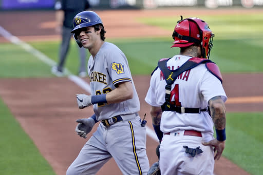 Milwaukee Brewers' Christian Yelich, right, smiles as he looks back at St. Louis Cardinals catcher Yadier Molina, right, after hitting a solo home run during the third inning in the first game of a baseball doubleheader Friday, Sept. 25, 2020, in St. Louis. (AP Photo/Jeff Roberson)