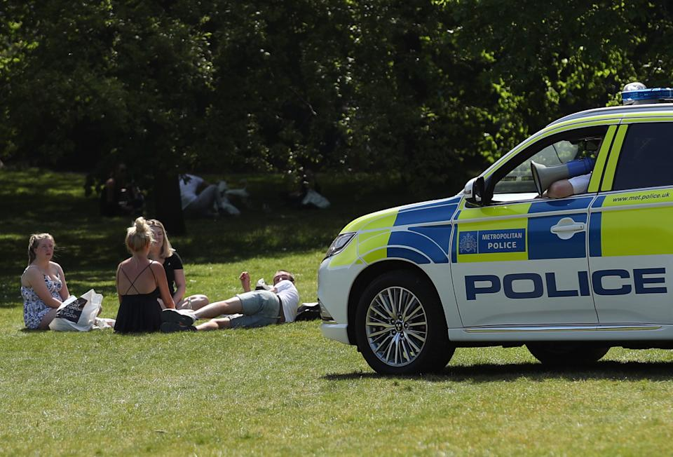 Police officers in a patrol car move sunbathers on in Greenwich Park, London, as the UK continues in lockdown to help curb the spread of the coronavirus. (Photo by Yui Mok/PA Images via Getty Images)