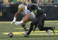 UCLA's Alec Anderson, left, and Oregon's Verone McKinley III scramble for a fumble during the first quarter of an NCAA college football game Saturday, Nov. 21, 2020, in Eugene, Ore. (AP Photo/Chris Pietsch)