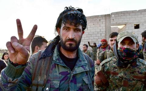 """Fighters from the Syrian Democratic Forces (SDF) gesture the """"V"""" for victory sign as they come back from the frontline in the Islamic State group's last remaining position in the village of Baghuz - Credit: AFP"""