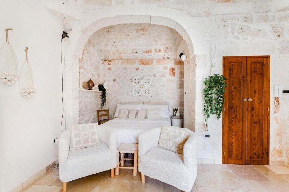 """While it's referred to as a tiny house, it's really a studio, and therefore much larger than the tiny houses that come to mind in the U.S. This quaint, stone-walled Puglia home is nearly all one open space, with a queen bed, armchairs, and a TV that make up the living space, a kitchen table that seats four, and a tucked-away kitchenette with a stovetop, mini-fridge, coffer maker, and essentials like utensils. A small staircase leads up to the terrace, a cozy spot to eat breakfast, enjoy apertivo hour, or lounge with a good book. From the house, it's a short walk to Ostuni's town square, which sits near the top of Italy's boot heel. $153, Airbnb (Starting Price). <a href=""""https://www.airbnb.com/rooms/plus/12459586"""" rel=""""nofollow noopener"""" target=""""_blank"""" data-ylk=""""slk:Get it now!"""" class=""""link rapid-noclick-resp"""">Get it now!</a>"""
