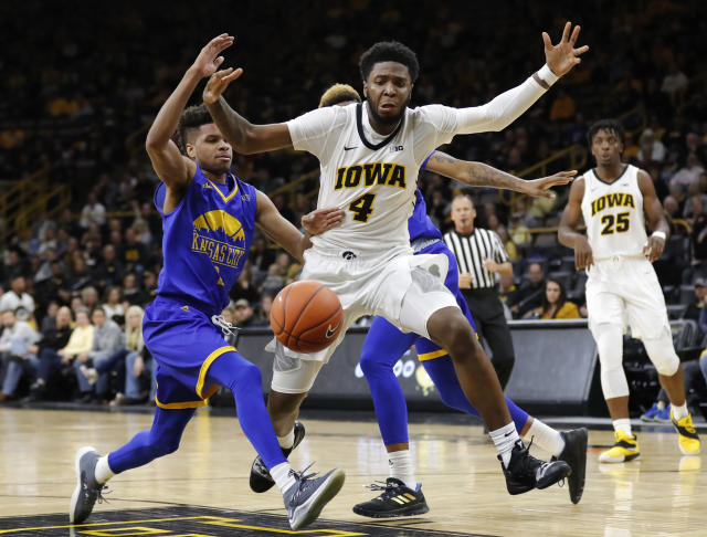 Iowa guard Isaiah Moss (4) loses the ball while driving to the basket ahead of UKMC guard Rob Whitfield, left, during the first half of an NCAA college basketball game, Thursday, Nov. 8, 2018, in Iowa City, Iowa.(AP Photo/Charlie Neibergall)