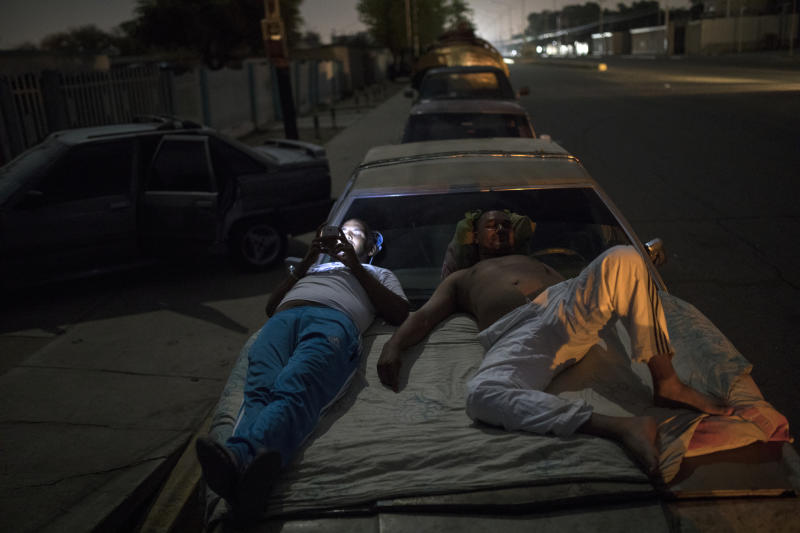Andres Quintero, left, and Fermin Perez rest on top of Perez's car as they wait in line for over 20 hours to fill their tanks with gas in Cabimas, Venezuela, Thursday, May 16, 2019. U.S. sanctions on oil-rich Venezuela appear to be taking hold, resulting in mile-long lines for fuel in the South American nation's second-largest city, Maracaibo. (AP Photo/Rodrigo Abd)
